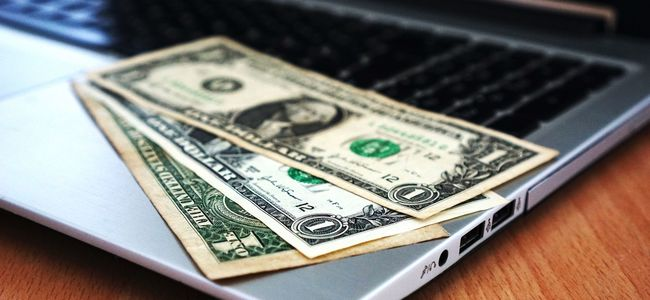 open laptop computer with dollar bills on it 2